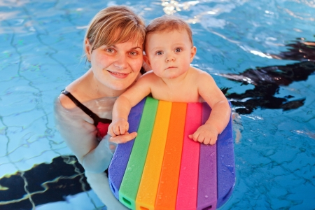 Cute baby with blue eyes learning to swim with mother