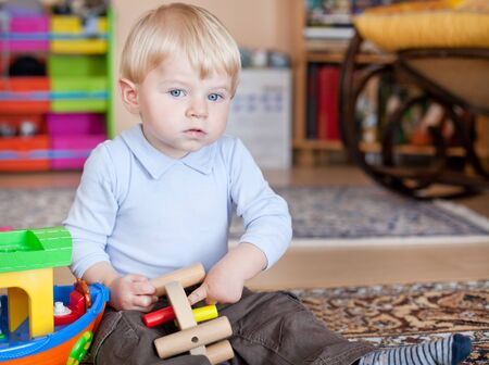 Little toddler boy playing with wooden toys indoor photo