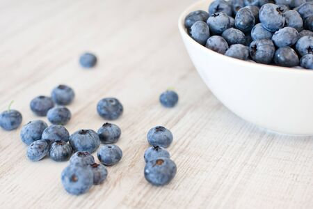 White bowl cup with fresh ripe blueberries  on wooden table Stock Photo - 16670900
