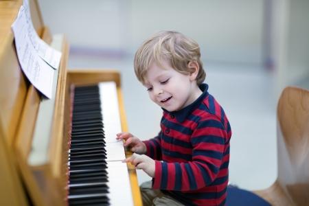 Prodigy: Dwóch lat szczęśliwy chłopiec maluch gra na fortepianie Zdjęcie Seryjne