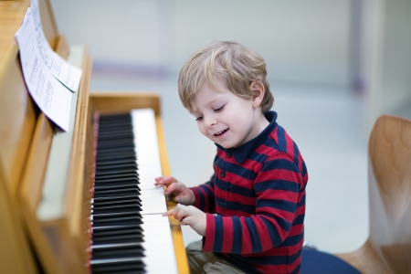 Two years old happy toddler boy playing piano photo
