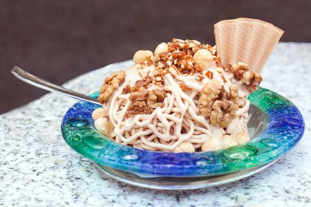 Nuts with fresh ice-cream and cream decorated with cone photo