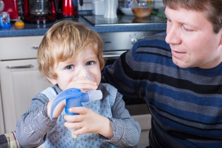 Little boy and his father making inhalation with nebuliser in home kitchen