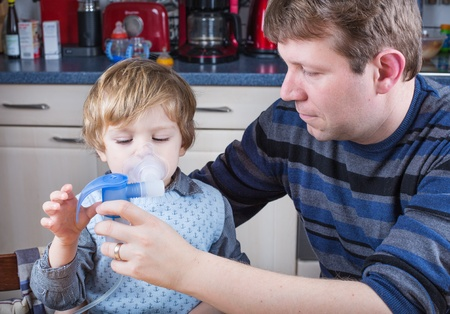 inhalation: Little boy and his father making inhalation with nebuliser in home kitchen