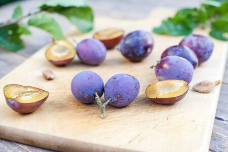 Fresh ripe plums on wooden cutting board and table in summer Stock Photo - 16754199