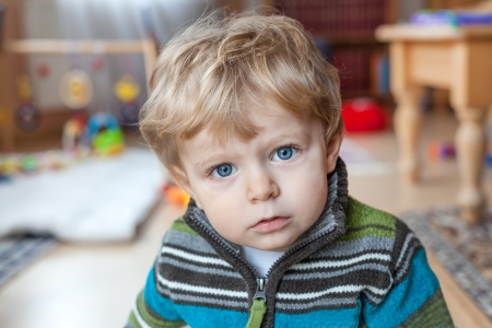 Adorable toddler with blue eyes and blond hair indoor Stock Photo