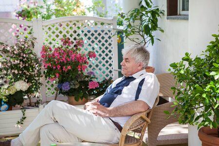 Senior man enjoying summer in flower garden Stock Photo - 16732320