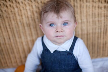 Adorable toddler with blue eyes and blond hair indoor photo