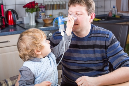 Beautiful boy and young man making inhalation with inhalator in home kitchen photo
