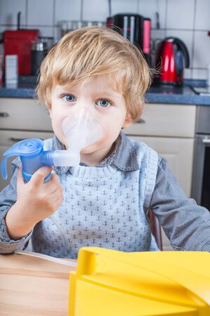 Adorable toddler boy making inhalation with nebulizer and inhalator in home kitchen photo