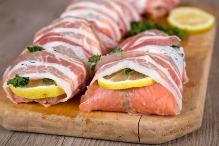 Fresh salmon wrapped with bacon prepared for grill on wooden cutting board photo