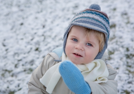 Adorable toddler boy on beautiful winter snowy day photo