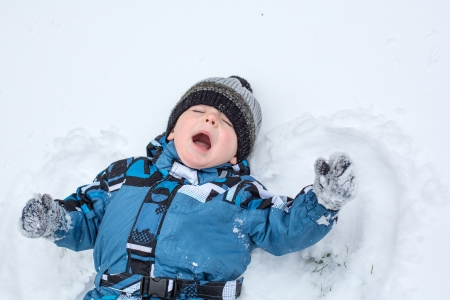 Adorable toddler boy making angel on snow in winter Stock Photo - 16829202