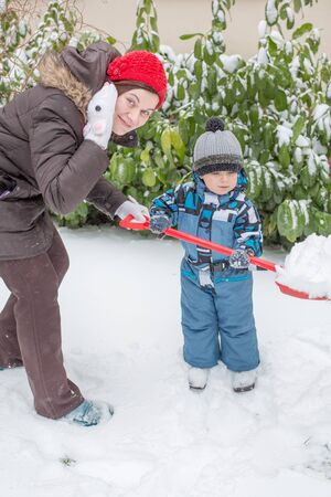 Young woman and little toddler boy having fun with snow outdoors on beautiful winter day Stock Photo - 16829211