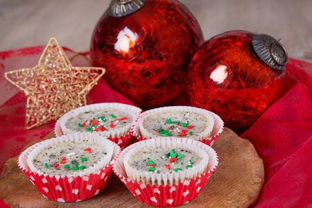 Fresh baked cookies and cream cheesecakes in muffin forms with red Christmas tree balls photo