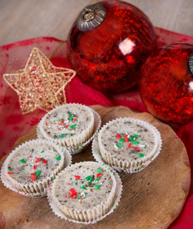 Fresh mini cookies and cream cheesecakes in muffin forms with red Christmas tree balls