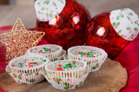 Sweet cookies and cream cheesecakes in muffin forms with red Christmas tree balls photo
