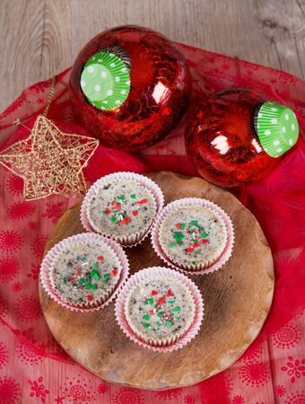 Sweet dessert - mini cheesecakes in muffin forms with red Christmas tree balls photo