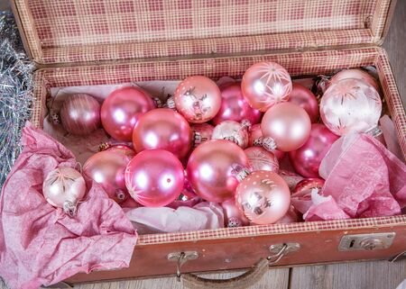 Ancient old pink Christmas tree toys in antique suitcase photo