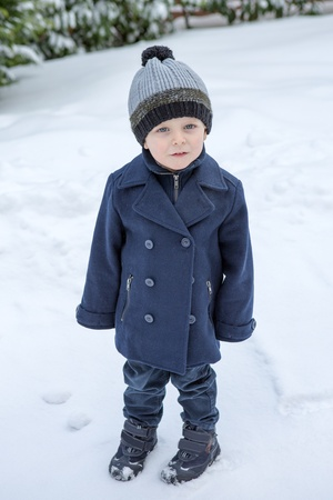 Little boy of two years in winter clothes on day with lot of snow photo