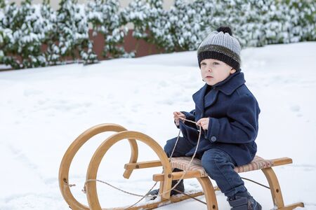 Lovely little boy on ancient sledge on winter snow day photo