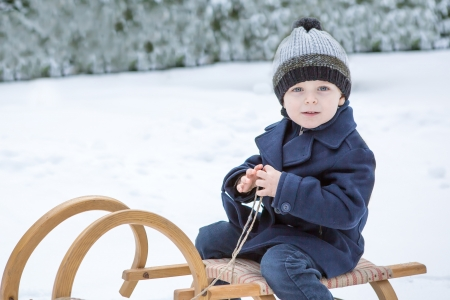 Cute little toddler boy on ancient sledge on winter snow day photo