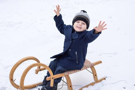 Lovely little boy having fun on ancient sledge on winter snow day photo