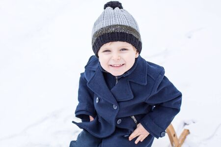 Portrait of cute toddler boy smiling on beautiful winter snowy day photo