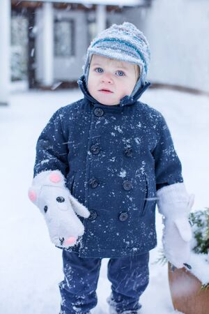 Portrait of adorable cute toddler boy smiling on beautiful winter snowy day photo