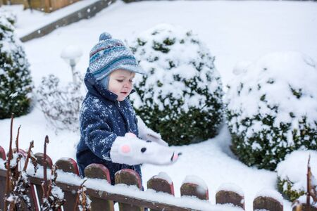 Little boy of one year having fun with snow on winter day during snowfall photo
