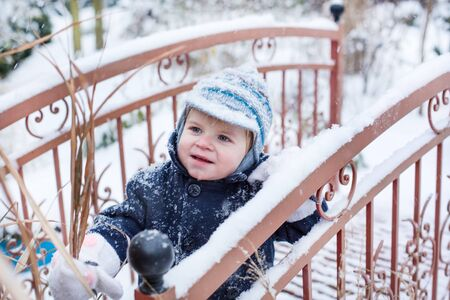 Adorable toddler boy of one year having fun with snow on winter day during snowfall photo