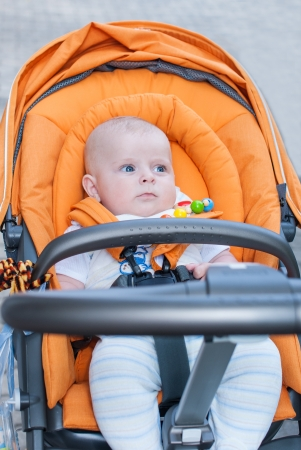 Lovely baby boy outdoor in orange stroller in summer photo