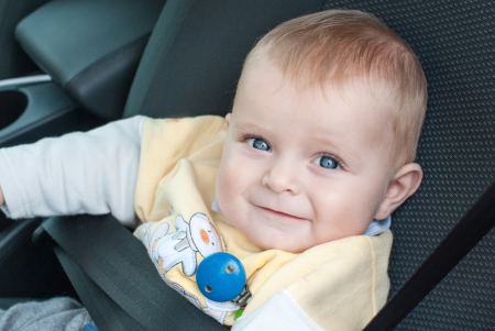 Adorable baby boy with blue eyes sitting in daddys car photo