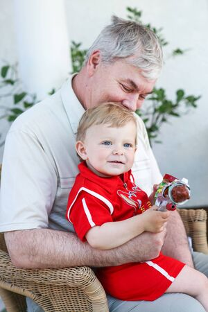 Grandfather with little baby boy sitting in summer garden Stock Photo - 16953478