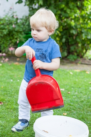 Little sweet toddler boy playing with toy in summer garden outdoors photo