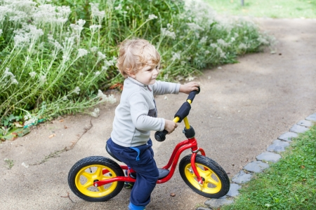 2 years old toddler child learning to ride on his first bike