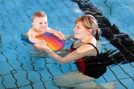 Little baby with blue eyes learning to swim with mother photo