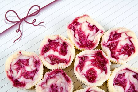 Fresh baked mini raspberry cheesecakes in muffin forms photo