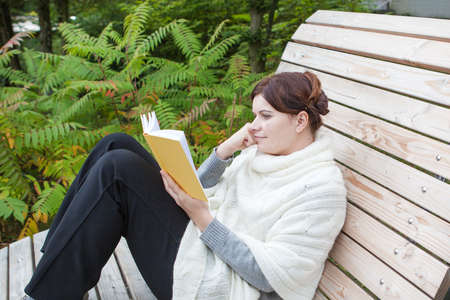 Beautiful woman reading book on bench in spring park photo