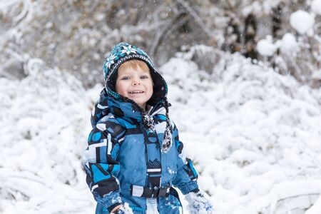 Little boy having fun with snow outdoors on beautiful winter day photo