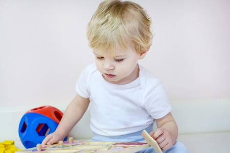 assiduous: Little toddler boy playing with wooden puzzle toys indoor