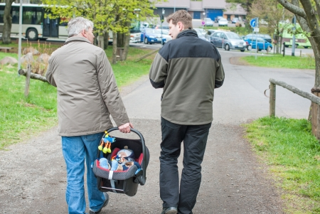 Grandfather and Father walking with little baby son in car seat Stock Photo - 17341476