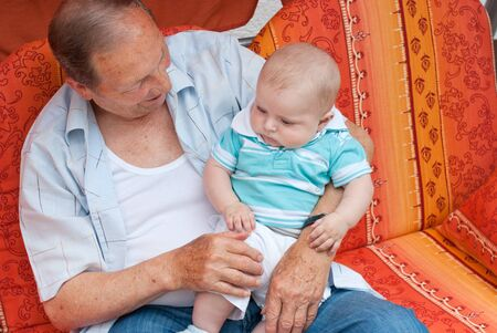 Grandfather with little baby boy sitting in summer garden Stock Photo - 17341464