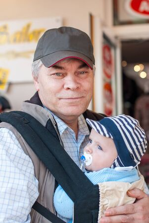 Grandfather with adorable little baby grandchild in rucksack Stock Photo - 17341380