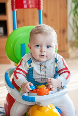Little baby boy playing with toy car indoor in kindergarten photo