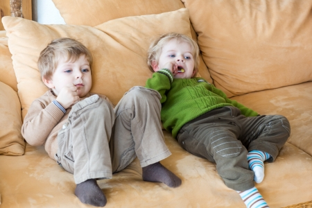Two little brother boys watching tv and eating candy indoor photo