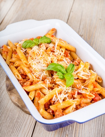 Italian pasta with meat sauce and parmesan cheese, served on a blue bowl and wooden background