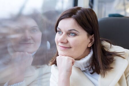 Young woman traveling by train and looking out the window outside, while it moving. travel Stock Photo