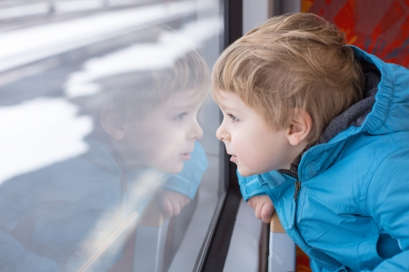 Cute little boy looking out train window outside, while it moving. travel photo