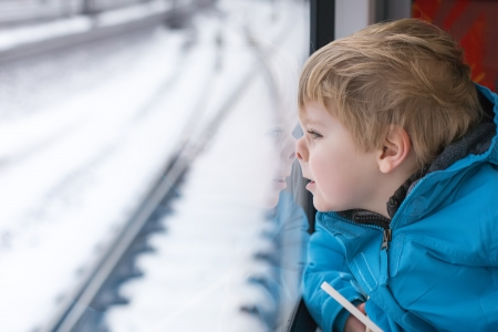 Beautiful toddler boy looking out train window outside, while it moving. travel